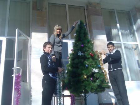 Никита и Рустам с классным руководителем наряжают новогоднюю ёлку