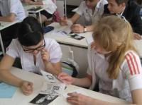 """Ученики 8 """"А"""" класса рассматривают фотографии с раскопок"""